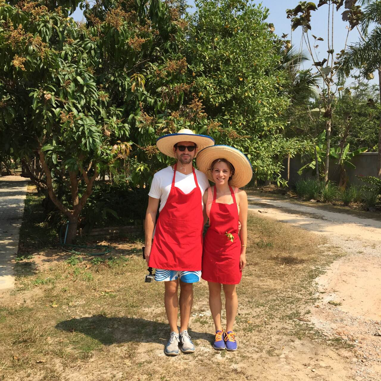 Thai cooking attire; red aprons and sombreros.